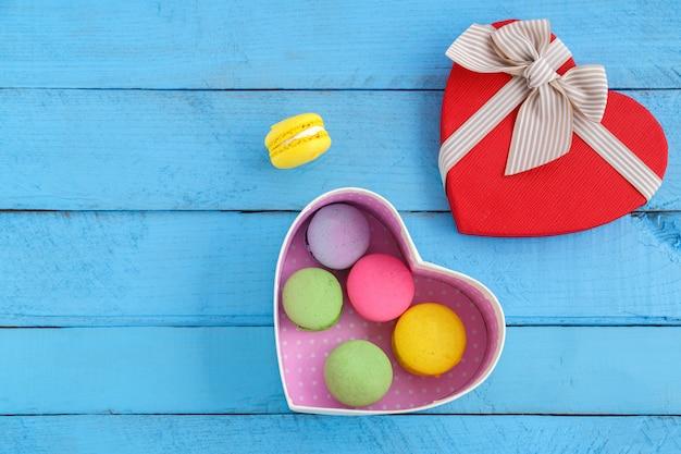 Kleurrijke macaronkoekjes en een hartvormige doos op een blauwe houten uitstekende achtergrond