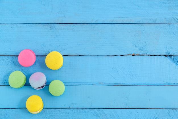 Kleurrijke macaronkoekjes op blauwe houten uitstekende lijst
