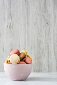 Kleurrijke macarons in een uitstekende kom op de witte houten ruimte van het lijstexemplaar