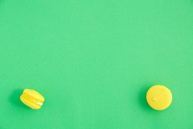 Kleurrijke macarons of makaronskoekjes op groene achtergrond