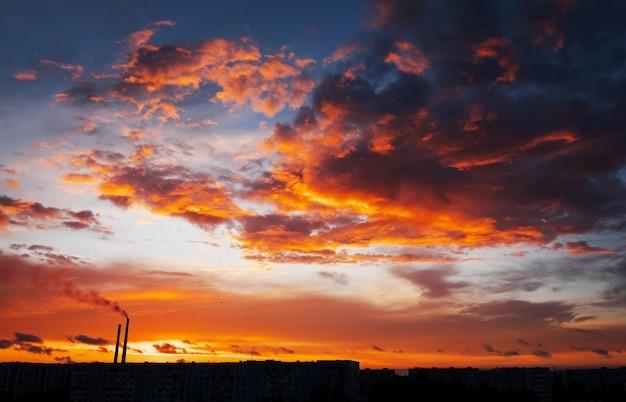 Kleurrijke magische zonsondergang. daken van stadshuizen tijdens zonsopgang. vogels die in de lucht vliegen. donkere rook uit de pijp van de thermische elektriciteitscentrale.