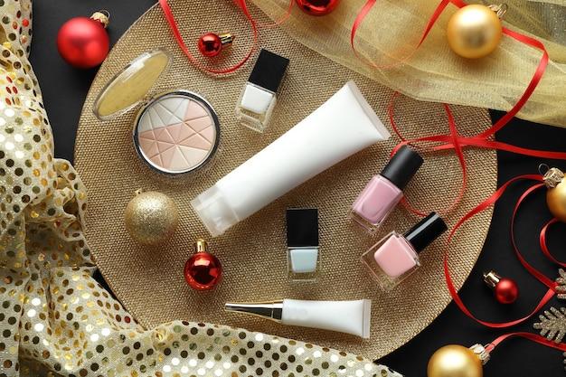 Kleurrijke make-upcosmetica met kerstversiering op gouden dienblad
