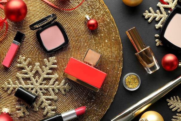 Kleurrijke make-upcosmetica met kerstversiering op mat met gouden kralen