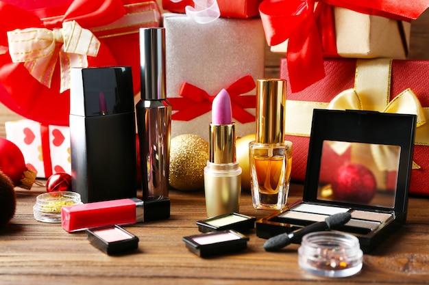 Kleurrijke make-upcosmetica met kerstversiering op wazig geschenkenoppervlak