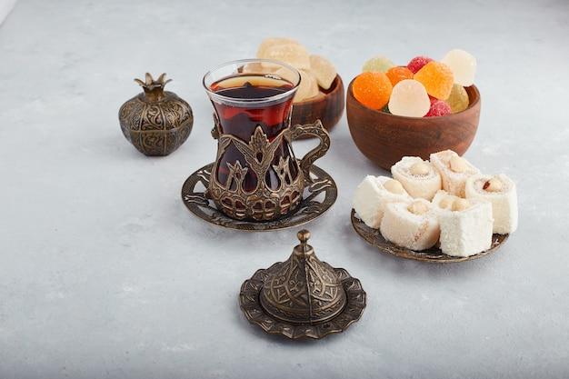 Kleurrijke marmelade lekkernijen in een houten kom met een glas thee op een witte ondergrond.