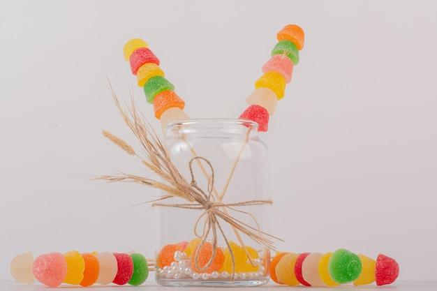 Kleurrijke marmelade sticks in glazen pot.