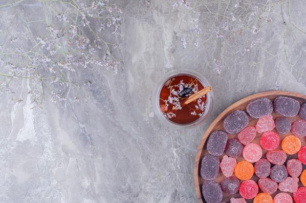 Kleurrijke marmelades in een houten schotel met een kopje thee.