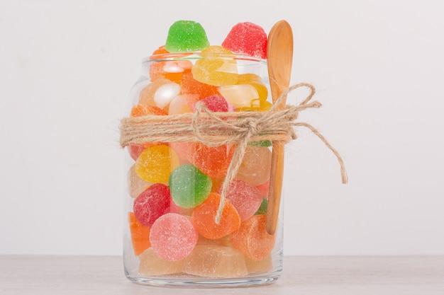 Kleurrijke marmelades in glazen pot met houten lepel.