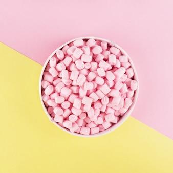 Kleurrijke marshmallow aangelegd op roze en geel papier oppervlak