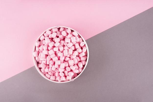 Kleurrijke marshmallow aangelegd op roze en grijs papier oppervlak