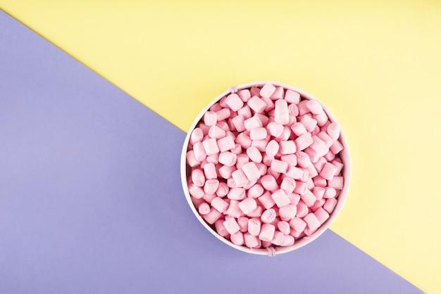 Kleurrijke marshmallow aangelegd op violet en geel papier oppervlak