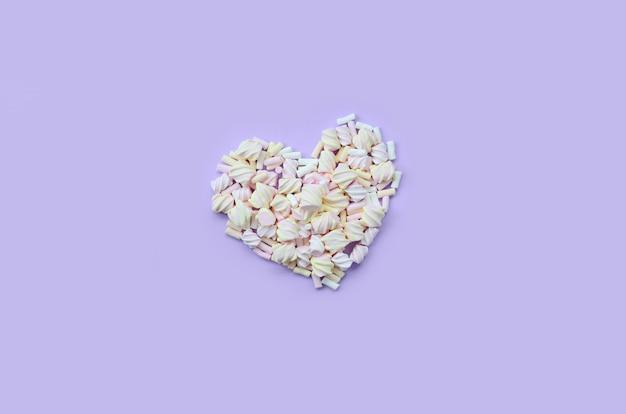 Kleurrijke marshmallow aangelegd op violet en roze papier