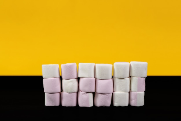 Kleurrijke marshmallow snoepjes op een gele en zwarte achtergrond. detailopname
