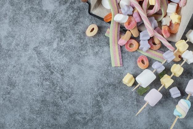 Kleurrijke marshmallows op de houten stokken om te grillen.