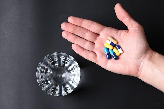 Kleurrijke medische pillen in de hand van een persoon en een glas water. bovenaanzicht