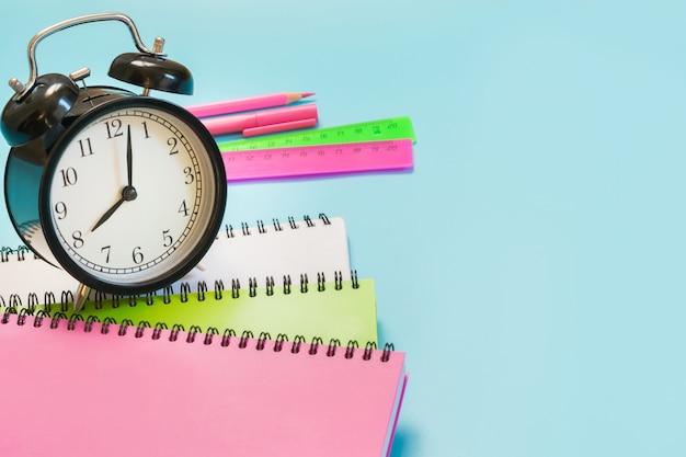 Kleurrijke meisjesachtige schoolbenodigdheden, boek en wekker op pittig blauw. detailopname. terug naar school.