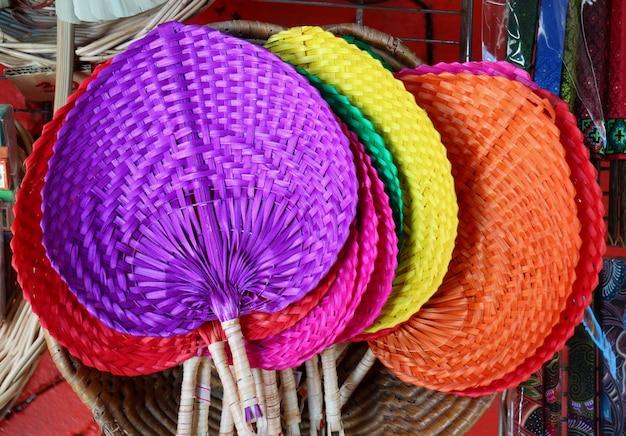Kleurrijke met de hand gemaakte natuurlijke die raffiaventilators in de winkel bij vlooienmarkt in thailand worden getoond