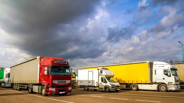 Kleurrijke moderne grote semi-vrachtwagens en trailers van verschillende merken en modellen staan in de rij op een vlakke parkeerplaats van vrachtwagenstopplaats in de zon