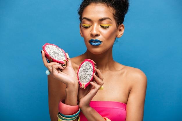Kleurrijke mooie gemengd rasvrouw met heldere schoonheidsmiddelen die op gezicht rijpe pitahaya houden die in de helft in beide geïsoleerde handen wordt gesneden, over blauwe muur