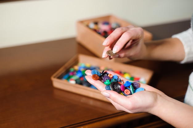 Kleurrijke naaien knoppen in de handen. kleurrijke knoppen