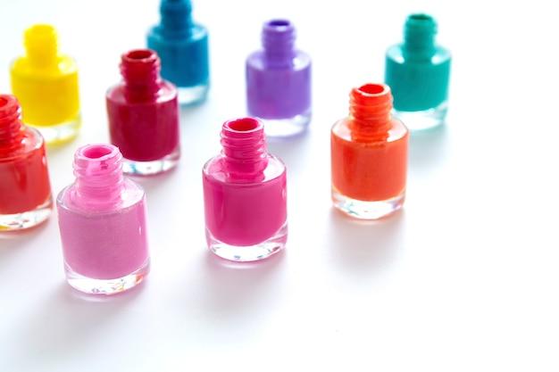 Kleurrijke nagellakflessen op wit, exemplaarruimte