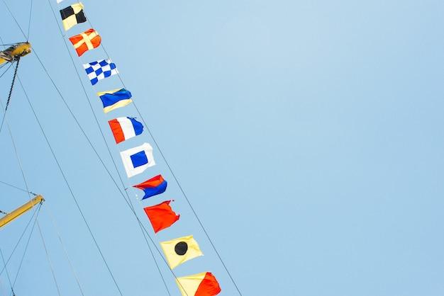 Kleurrijke nautische zeilvlaggen die in de wind vliegen vanaf de lijnen van een zeilbootmast die door de zon in de heldere blauwe lucht wordt verlicht.