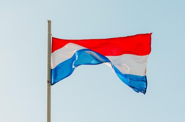 Kleurrijke nederland vlag zwaaien op blauwe hemel.