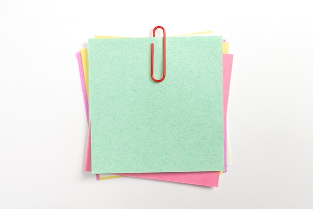 Kleurrijke notitie papier pin met rode paperclips en geïsoleerd op wit.
