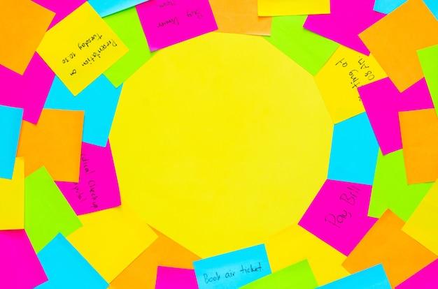 Kleurrijke notitieblaadjes om dagelijkse activiteit op gele achtergrond te herinneren.
