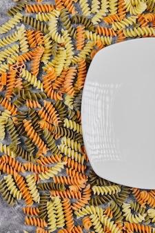 Kleurrijke ongekookte fusilli naast witte plaat op wit.