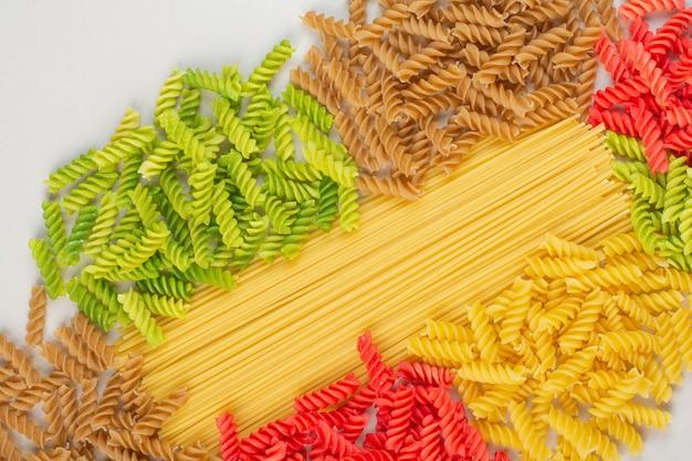 Kleurrijke ongekookte spiraalvormige deegwaren en spaghetti op witte oppervlakte