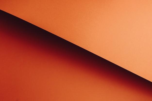 Kleurrijke oranje plat lag achtergrond met scherpe lagen en schaduwen met kopie ruimte