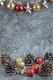 Kleurrijke ornamenten opgehangen aan de rustieke draad op betonsteen met eikenboomkegels eromheen