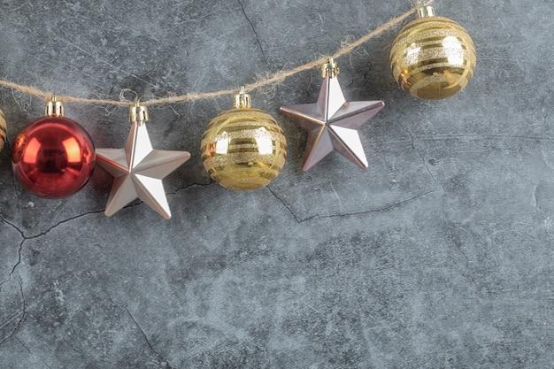 Kleurrijke ornamenten opgehangen aan de rustieke draad op grijs