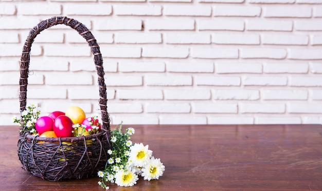 Kleurrijke paas eieren in bruin mand met bloem