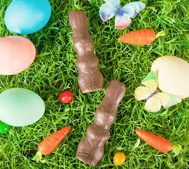 Kleurrijke paaseieren, chocoladekonijntje, wortelsuikergoed in het gras. bovenaanzicht.