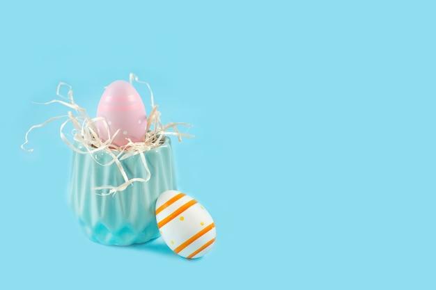 Kleurrijke paaseieren en blauwe vaas op blauwe achtergrond