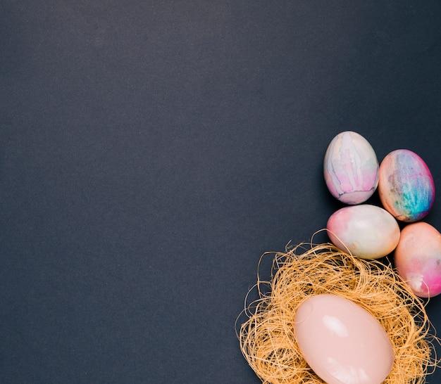 Kleurrijke paaseieren en roze ei op het nest over de hoek van de zwarte achtergrond