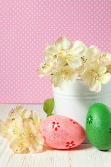 Kleurrijke paaseieren en tak met bloemen in kleine witte emmer op roze stippenachtergrond.