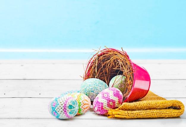 Kleurrijke paaseieren gemorst uit het nest in een rode emmer met stof op een houten tafel. gelukkig pasen