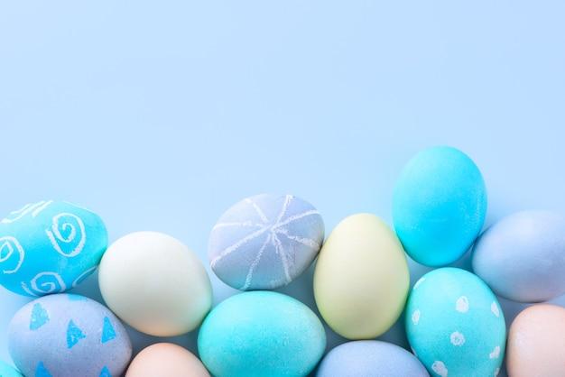 Kleurrijke paaseieren geverfd door gekleurd water met prachtig patroon op een lichtblauwe achtergrond, ontwerpconcept van vakantie-activiteit, bovenaanzicht, kopieerruimte.
