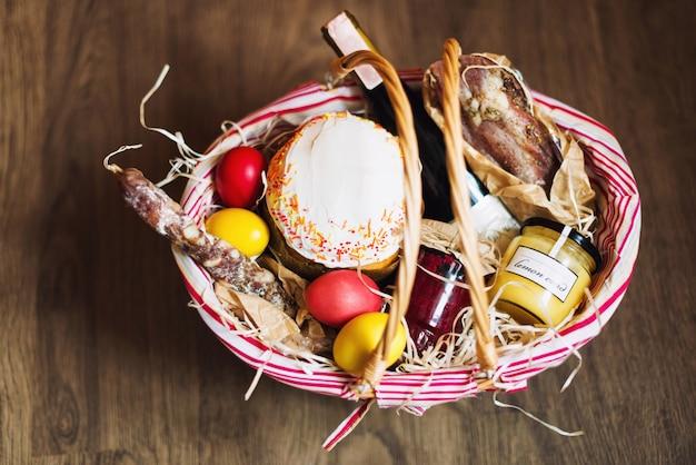 Kleurrijke paaseieren in een mand met cake, rode wijn, hamon of schokkerige en droge rookworst
