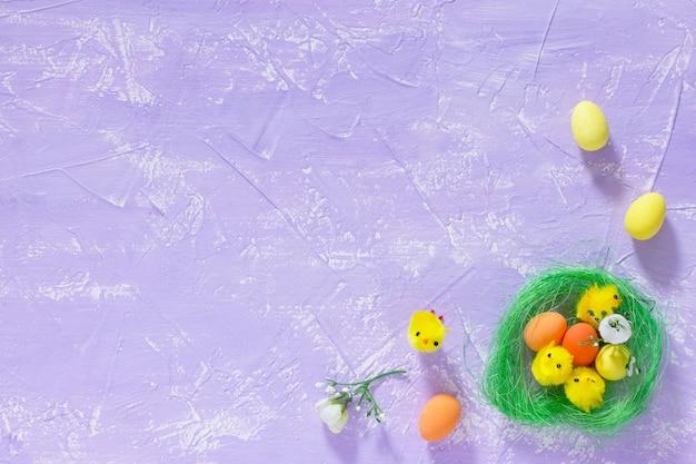 Kleurrijke paaseieren in het nest en kuikens