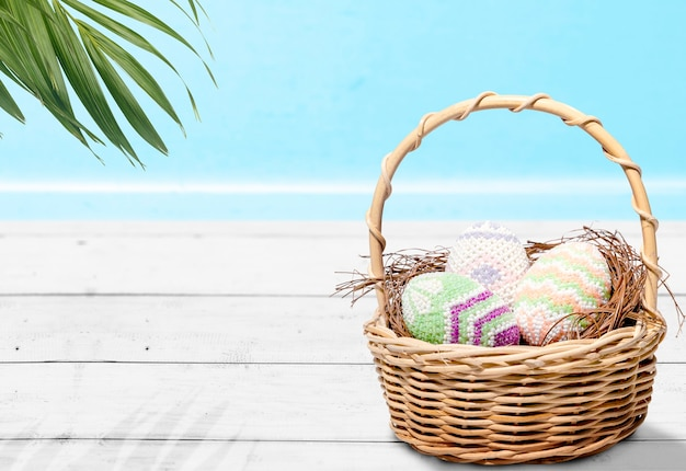 Kleurrijke paaseieren in het nest op een houten mand op tafel. gelukkig pasen