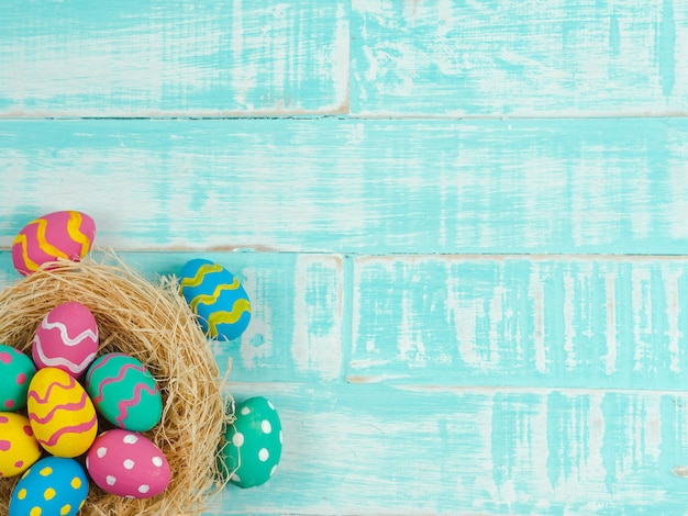 Kleurrijke paaseieren in het nest op houten achtergrond