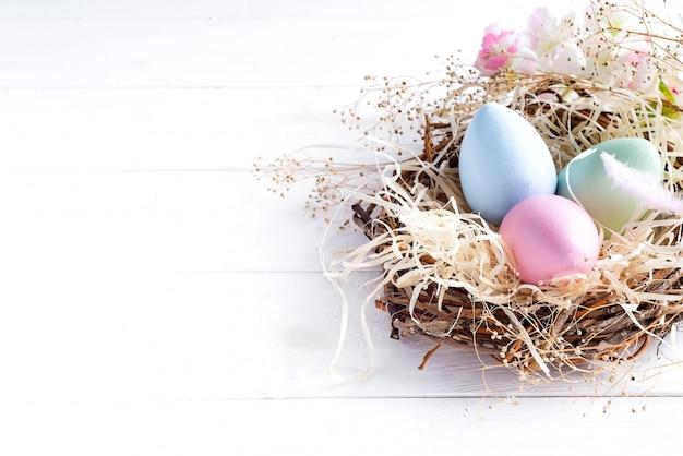 Kleurrijke paaseieren in klein nest met op witte houten achtergrond, exemplaarruimte. vakantie evenement