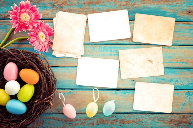 Kleurrijke paaseieren in nest met bloem en leeg oud document fotoalbum op houten lijst
