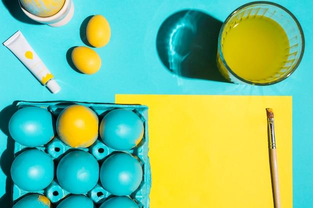 Kleurrijke paaseieren in rek met verfborstel, glas water en document