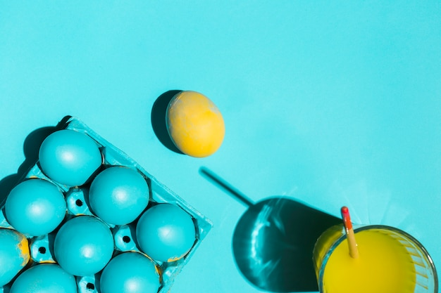 Kleurrijke paaseieren in rek met verfborstel in glas water