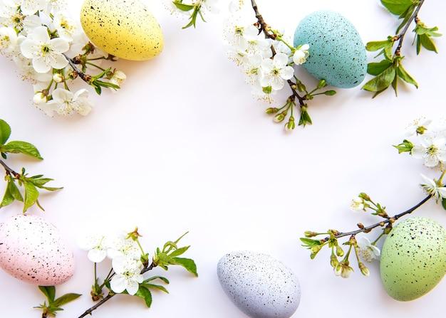 Kleurrijke paaseieren met bloesem lentebloemen geïsoleerd op witte achtergrond. gekleurde ei vakantie grens.